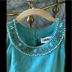 Aqua blue halter top with white and gold beading.